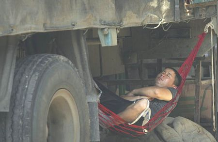 Водитель грузовика в Гуанчжоу прилег отдохнуть. Фото: AFP/Getty Images