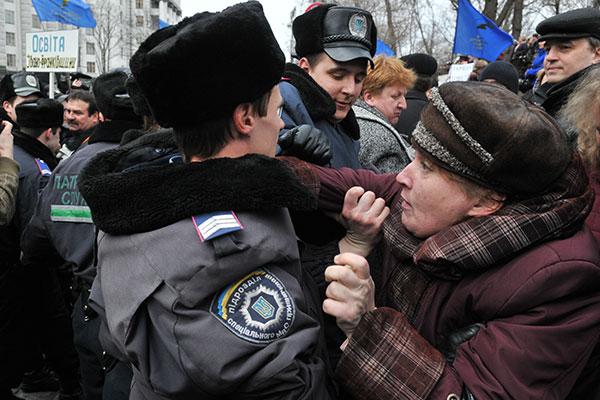 Милиция вытесняет с проезжей части участника акции работников сферы образования и науки с требованием повышения зарплаты возле Кабинета Министров Украины 22 марта 2011 года. Фото: Владимир Бородин/The Epoch Times Украина