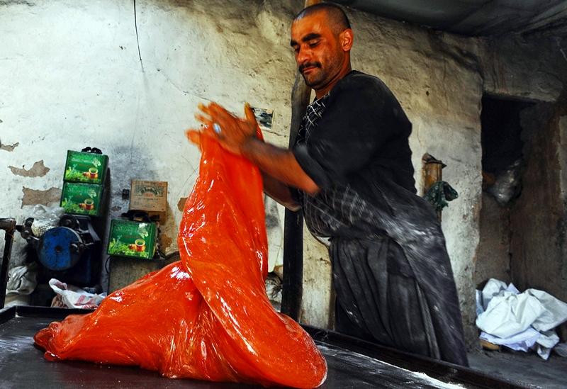 Герат, Афганістан, 14 травня. Робочий кондитерської фабрики виготовляє традиційні солодощі. Фото: Aref Karimi/AFP/Getty Images