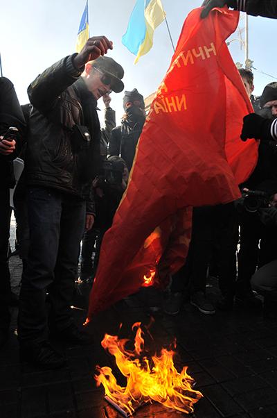 Мужчина сжигает флаг КПУ на акции протеста студентов в Киеве 28 февраля против принятия нового закона «О высшем образовании» и за отмену распоряжения о сокращении госзаказа на 42%. Фото: Владимир Бородин/The Epoch Times Украина