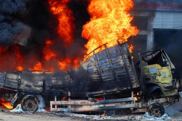 Грузовик, который подожгла толпа чернорабочих, горит у края дороги в городе Лудиана, Индия. Рабочие протестовали против отказа полиции расследовать три случая воровства зарплаты, полученной после отработанной недели. Фото: STR/AFP/Getty Images
