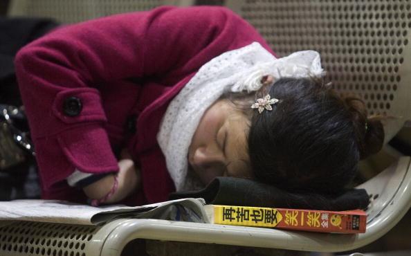 Девочка заснула, ожидая поезд, подложив под голову книгу с названием «Как бы не было горько, всё равно нужно улыбаться». Шанхай. 21.01.09. Фото: China Photos/Getty Images