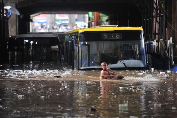 Транспорт оказался в ловушке на затопленной улице после сильного дождя в г. Ухань провинции Хубэй. Фото: ChinaFotoPress/Getty Images