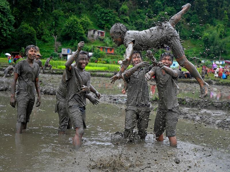 Покхара, Непал, 29 июня. Молодёжь веселится на рисовых полях во время празднования национального дня посадки риса. Фото: PRAKASH MATHEMA/AFP/Getty Images