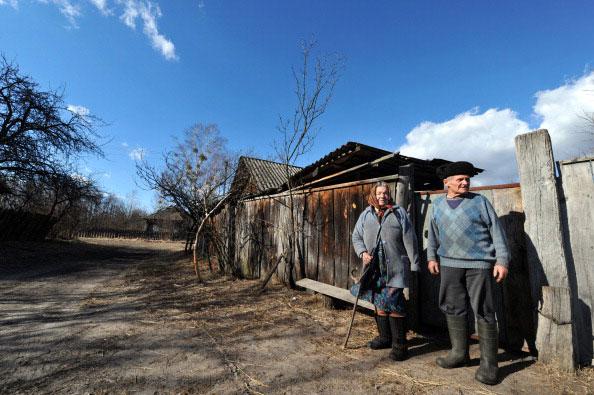 Иван Семенюк 75 лет и его жена Мария 73, стоят возле своего дома в заброшенной деревне Парышив в 30 киллометровой зоне отчуждения вокруг Чернобыльской АЭС 23 марта 2011 года. (SERGEI SUPINSKY/AFP/Getty Images)