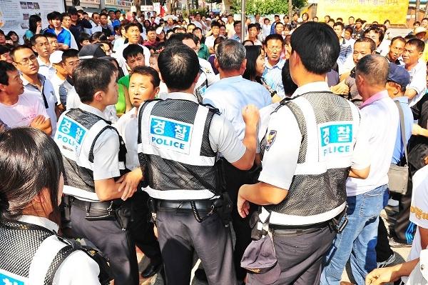 Обвинувачений Цуй намагається напасти на співробітників правопорядку. Фото: Guohuan Jin/The Epoch Times