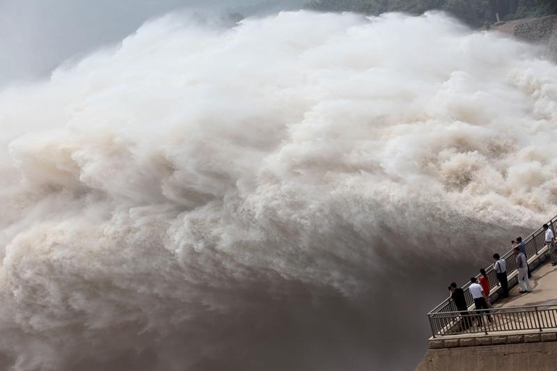 Сяоланди, провинция Хэнань, Китай, 23 июля. Жители наблюдают за сбросом воды из водохранилища. Уровень воды в резервуаре резко возрос из-за дождей, которые принёс тайфун «Соулик». Фото: STR/AFP/Getty Images