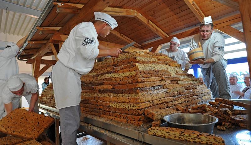 Дрезден, Германия, 2 декабря. Пекари из Ассоциации традиционной выпечки изготавливают гигантский фруктовый кекс, который будет продан 8 декабря на 19-м фестивале кексов. Фото: MATTHIAS HIEKEL/AFP/Getty Images