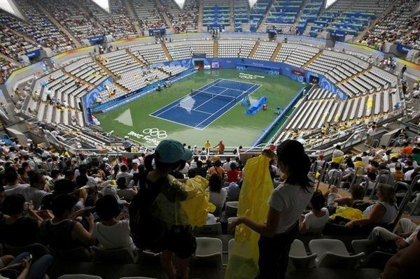 На стадионе зрители ждут, когда прекратится дождь, чтобы посмотреть прерванные соревнования 10 августа 2008 г., Пекин. Фото: BEHROUZ MEHRI/AFP/Getty Images