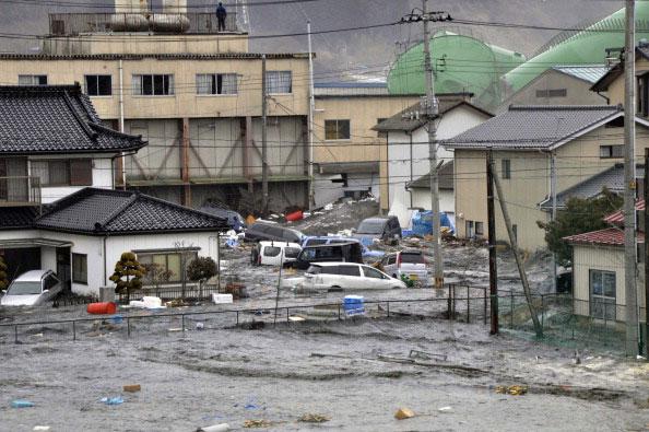 Приливные волны цунами разбивают автомобили и дома в городе Kesennuma в префектуре Мияги, после сильного землетрясения в Японии 11 марта 2011 года. Фото: AFP PHOTO / YOMIURI SHIMBUN
