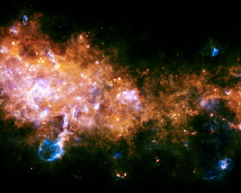 Образование звёзд в нашей галактике (созвездие Орла). В центре и слева — яркие области формирования сотен звёзд G29.9 и W43. Горячие светила области W43 выдувают в пространство вещество в виде огромного пузыря (слева внизу). Фото: ESA/Hi-GAL Consortium