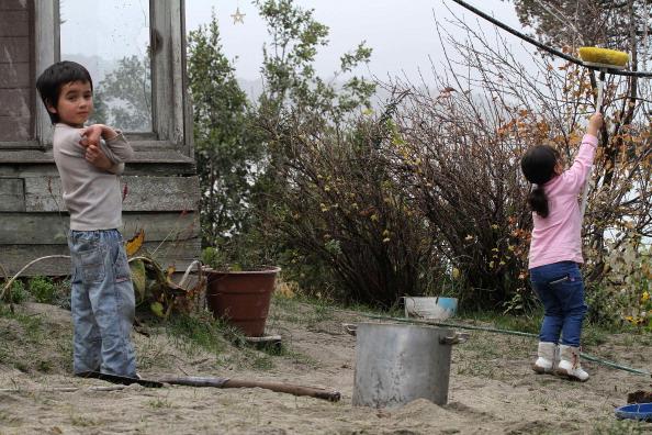 Дети убирают вулканический пепел в саду дома, расположенном в городе-курорте Барилоче, Аргентина. Фото: Francisco Ramos Mejia/AFP/Getty Images
