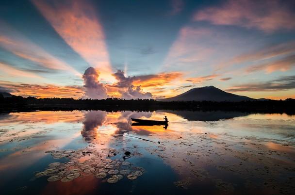 Лучи восходящего Солнца. Озеро Сампалок, Филиппины. Фото: Danilo Dungo/travel.nationalgeographic.com