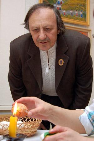 Мужчина наблюдает за изготовлением крашенки. Фото: Владимир Бородин/Великая Эпоха