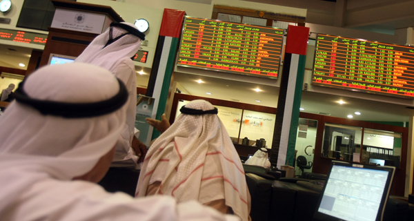 Араби з Об'єднаних Арабських Емірат стежать за змінами на фінансовому ринку Дубаї в Еміратській затоці. Фото: KARIM SAHIB / AFP / Getty Images