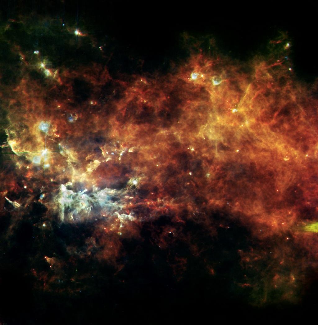 Конвейер «сборки звёзд» в созвездии Лисички — от горячего газа (оранжевый цвет) до нитей охлаждённого вещества (голубой цвет) и вкраплений новых ярких звёзд. Фото: ESA/Hi-GAL Consortium