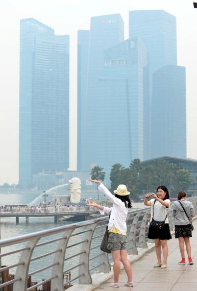 Люди фотографують місто, оповите смогом. Фото: ROSLAN RAHMAN/AFP/Getty Images