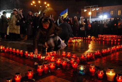 Женщина ставит свечку в знак скорби о  своих родственниках, которые погибли от голода. Фото: Владимир Бородин/ Великая Эпоха
