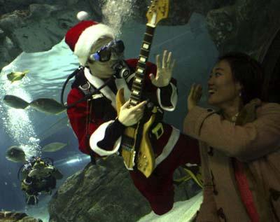 Водолази в костюмах Санта Клауса плавають в акваріумі Коекс у Сеулі. Фото: Чун Сун Жун/Getty Images