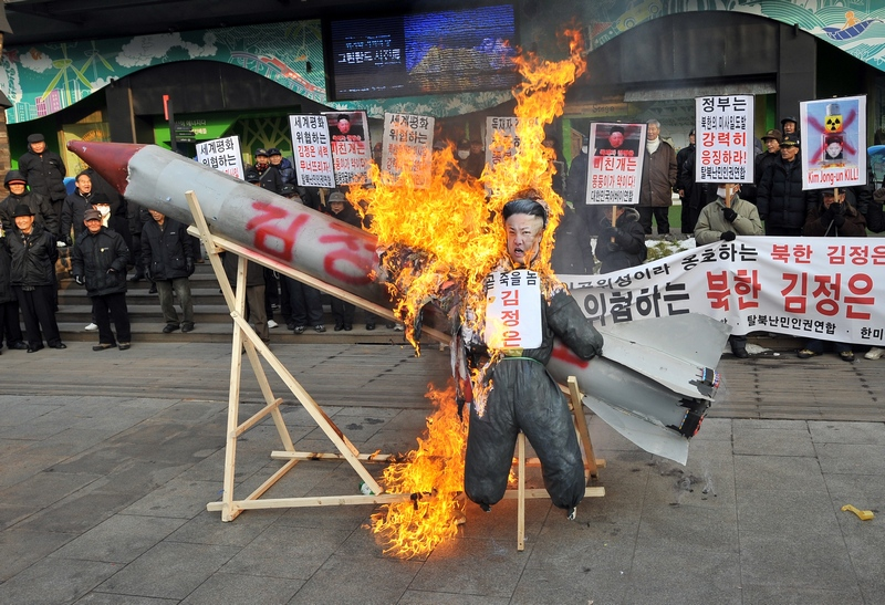 Сеул, Южная Корея, 13 декабря. Демонстранты сжигают картонную модель ракеты и куклу северокорейского лидера в знак протеста против запуска северянами ракеты со спутником на борту. Фото: JUNG YEON-JE/AFP/Getty Images
