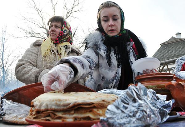 Девушка берет блин на праздновании Масляной в Мамаевой слободе. Фото: Владимир Бородин/The Epoch Times Украина