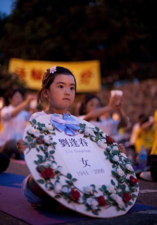Нью-Йорк, США. Девочка держит табличку с именем одного из последователей Фалунь Дафа, который был замучен до смерти в ходе репрессий в отношении последователей Фалунь Дафа в Китае. Фото: Великая Эпоха