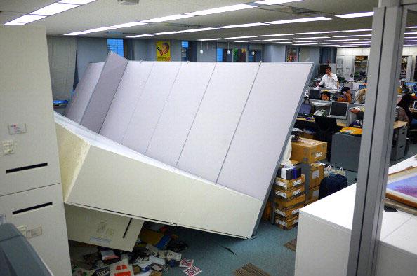 Люди продолжают работать в офисе с упавшими шкафами после повторных толчков от сильного землетрясения в Японии в Токио 11 марта 2011 года. Фото: AFP PHOTO / HIROKI 'DUKE' KOBAYASHI