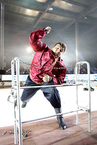 Дмитрий Халаджи перебивает цепь во время Всемирного фестиваля богатырской силы 19 декабря 2010 года в Киеве. Фото: Владимир Бородин/The Epoch Times Украина