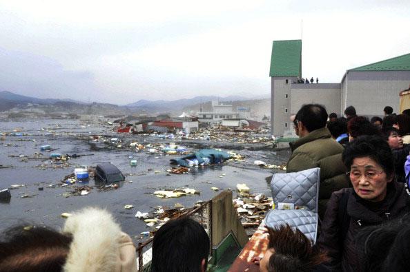 Люди смотрят на разбитые дома и машины после цунами в городе Kesennuma в префектуре Мияги, после сильного землетрясения в Японии 11 марта 2011 года. Фото: AFP PHOTO / YOMIURI SHIMBUN