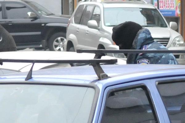 Грабитель садится в автомобиль после нападения на пункт обмена валют. Фото: Владимир Бородин/The Epoch Times Украина