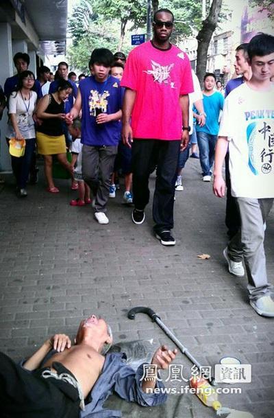 На вулиці міста Веньчжоу лежить старий, поруч проходить зірка НБА Карл Лендрі. Китайська провінція Чжецзян. Вересень 2011. Фото: news.ifeng.com
