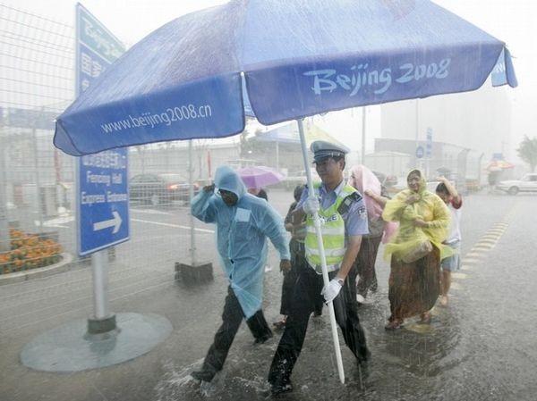 Китайская милиция с зонтиками провожает иностранных спорстменов 10 августа 2008 г., Пекин. Фото: AFP