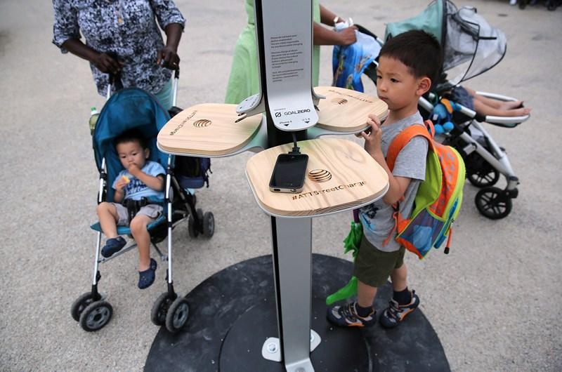 Нью-Йорк, США, 18 червня. Компанія AT&T встановила в місті 25 станцій безкоштовної підзарядки смартфонів енергією сонця. Кожна станція дозволяє заряджати одночасно до 6 пристроїв. Фото: John Moore/Getty Images