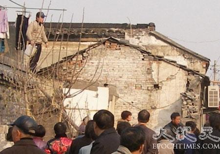 Сюэ Сянбяо на крыше своего дома угрожает совершить самосожжение, если дом не прекратят сносить. Фото: Великая Эпоха
