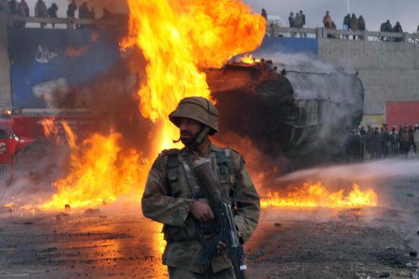 Пакистанский солдат стоит возле горящего нефтяного танкера НАТО после военных действий в Пешаваре 1 февраля 2010. Фото: HASHAM AHMED/AFP/Getty Images)