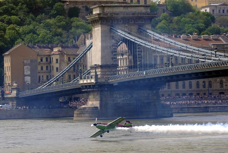 Будапешт, Угорщина, 1 травня. Чемпіон Європи з вищого пілотажу Золтан Вереш пролітає під найстарішим мостом через річку Дунай під час повітряного шоу. Фото: ATTILA KISBENEDEK/AFP/Getty Images