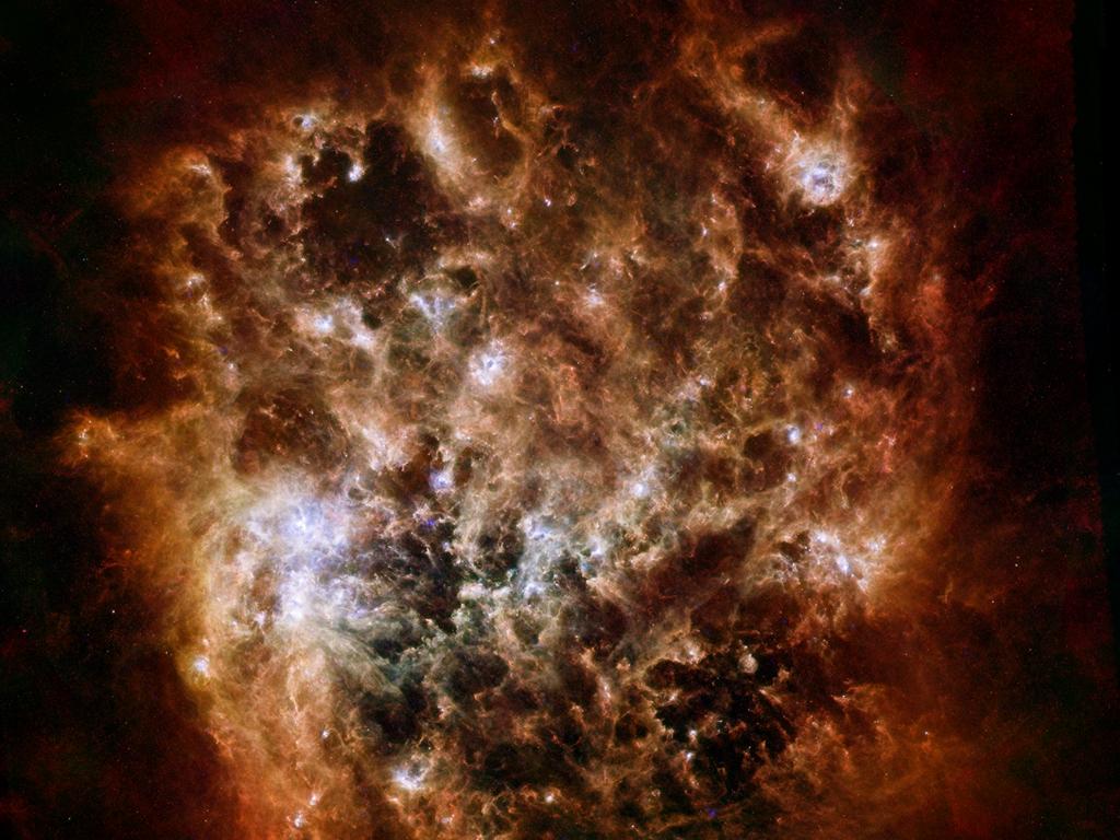 Похожие на пламя костра волны пыли в Большом Магеллановом Облаке. Яркая область слева по центру — туманность Тарантул, где происходят активные процессы образования светил. Фото: ESA/NASA/JPL-Caltech/STScI
