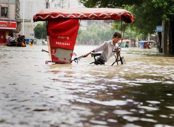 Человек везет велосипед по воде в г. Ланси, восточная китайская провинция Чжэцзян. Фото: STR/AFP/Getty Images