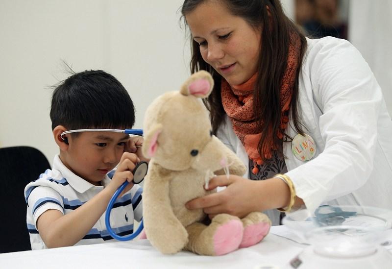 Берлин, Германия, 8 мая. Студентка-медик помогает 5-летнему малышу провести обследование своей игрушки в клинике лечения плюшевых медведей. Такие мероприятия помогают детям знакомиться с миром медицины. Фото: Sean Gallup/Getty Images