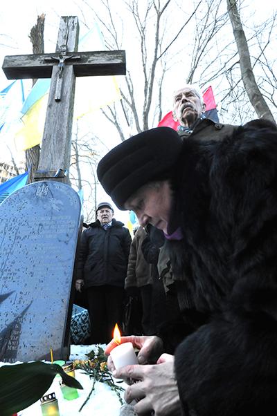 Женщина ставит свечку во время памятной акции возле памятника Героев Крут на Аскольдовой могиле в Киеве 29 января 2011 года. Фото: Владимир Бородин/The Epoch Times