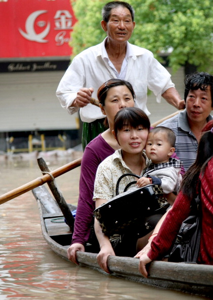 Люди плывут в лодке в г. Ланси, провинция Чжэцзян. Фото: STR/AFP/Getty Images
