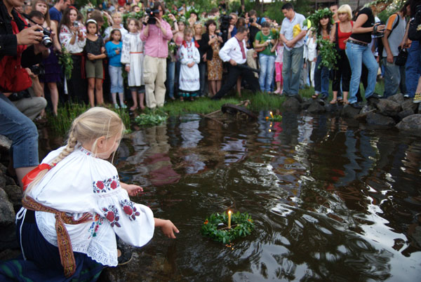 Девушки выпускают в воду сплетенные венки. Фото: Владимир Бородин/The Epoch Times