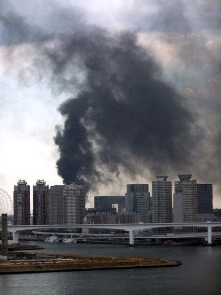 Черный дым поднимает над зданиями на набережной Daiba Токио в Токио после сильного землетрясения в Японии 11 марта 2011 года. Фото: AFP PHOTO / JIJI PRESS