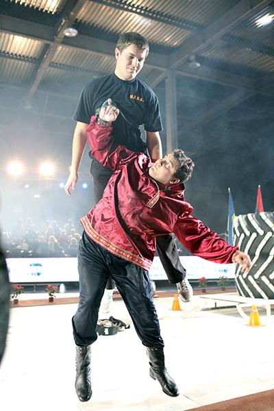 Дмитрий Халаджи одним мизинцем поднимает ассистента во время Всемирного фестиваля богатырской силы 19 декабря 2010 года в Киеве. Фото: Владимир Бородин/The Epoch Times Украина