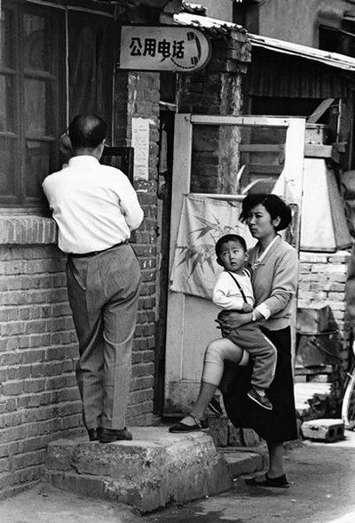 Женщина с ребёнком ждёт своей очереди возле общественного телефона. Фото с epochtimes.com