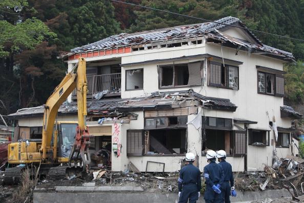 Полицейские наблюдают за уборкой обломков перед разрушенным домом. г. Отсучи, префектура Иватэ. Фото: Kiyoshi Ota/Getty Images