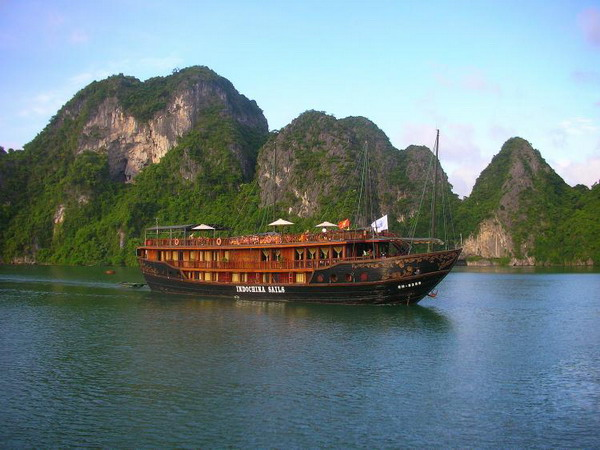 Деревянная джонка (плоскодонная лодка), Indochina Sails, скользит мимо известняковых островов, выступающих из изумрудных вод бухты Халонг. Фото с сайта theepochtimes.com