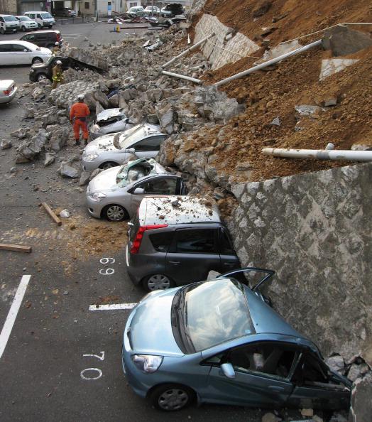 Разбитые автомобили под обрушившейся стеной на парковке в городе Мито в префектуре Ибараки 11 марта 2011 г. после сильного землетрясения в Японии. Фото: AFP PHOTO / JIJI PRESS