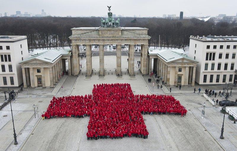 Берлін, Німеччина, 13січня. Близько 1800співробітників Німецького Червоного Хреста утворили фігуру хреста біля Бранденбурзьких воріт на честь 150-річчя організації. Фото: JOHN MACDOUGALL/AFP/Getty Images