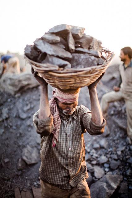 Чоловік несе наповнений вугіллям кошик. Фото: Daniel Berehulak/Getty Images